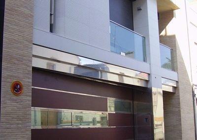 Frente de fachada con puerta combinada de vidrio, madera e inoxidable; balcón de inoxidable y vidrio; reja y marquesina de acero inoxidable